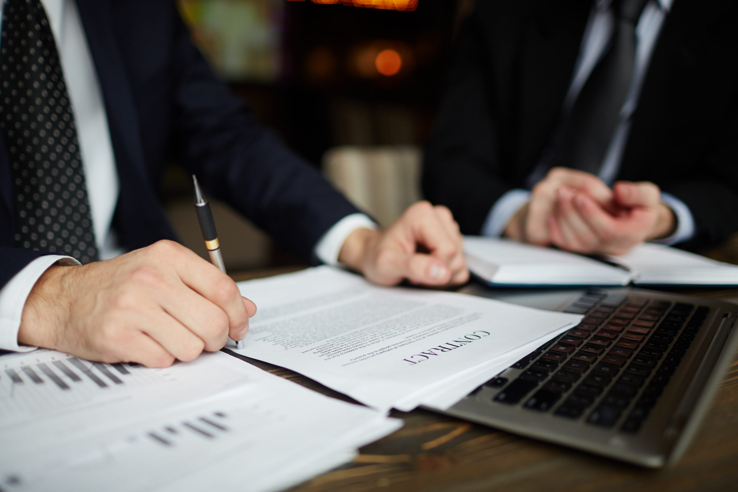 Closeup portrait of unrecognizable successful businessman wearing black formal suit reviewing documents and signing contract during meeting